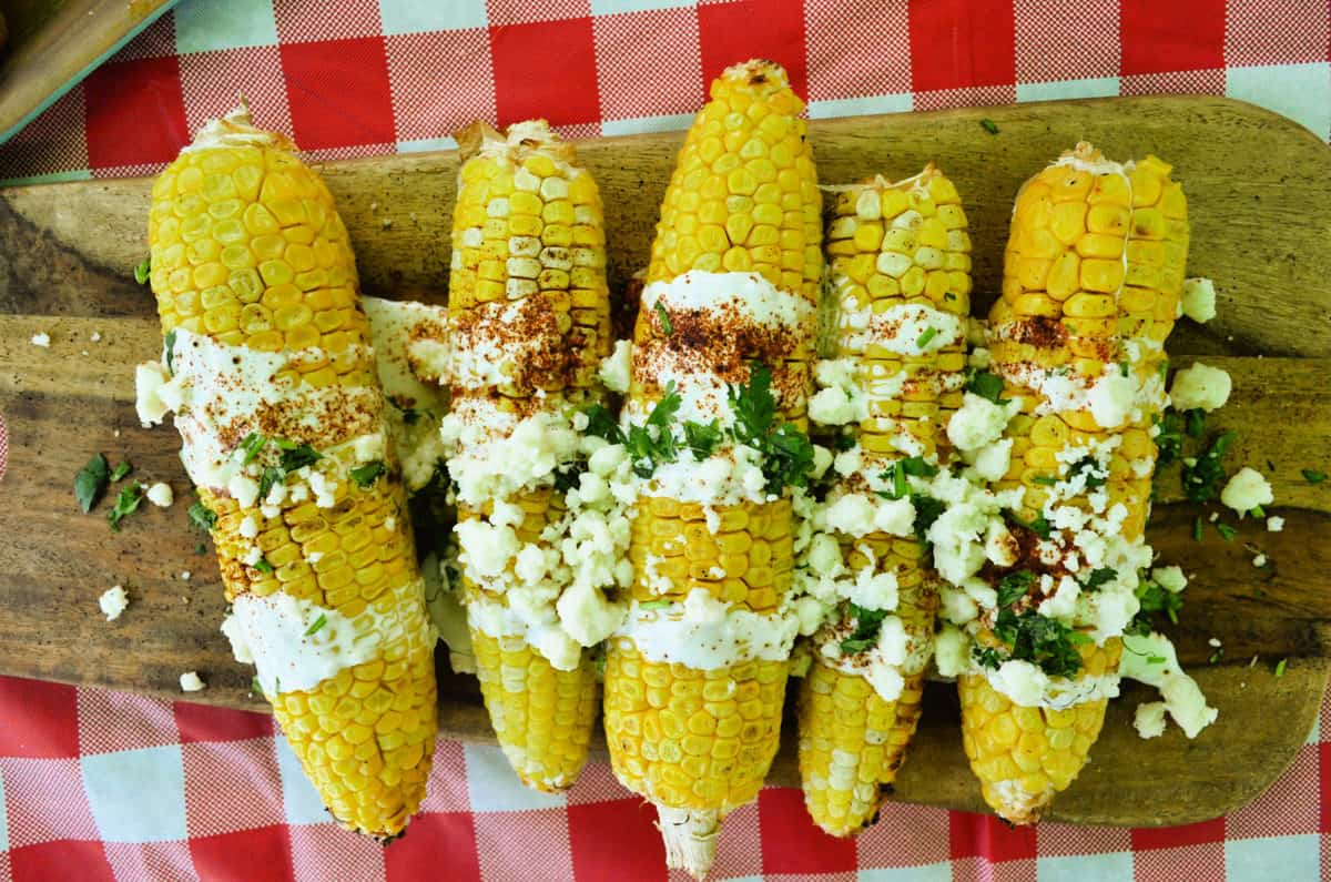 horizontal view of corn cobs on a board drizzled with crema, cheese crumbles, and herbs.