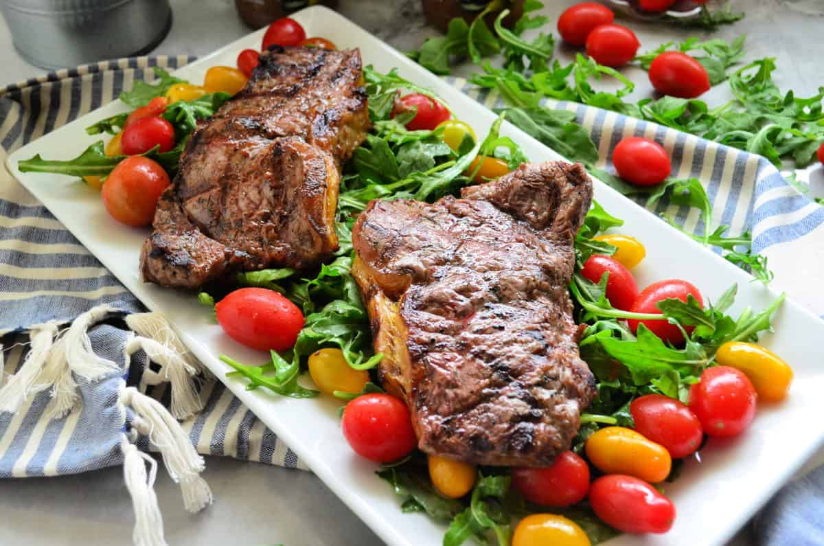 2 cooked steaks over bed of arugula salad with grape tomatoes on rectangular platter on tablelcoth.