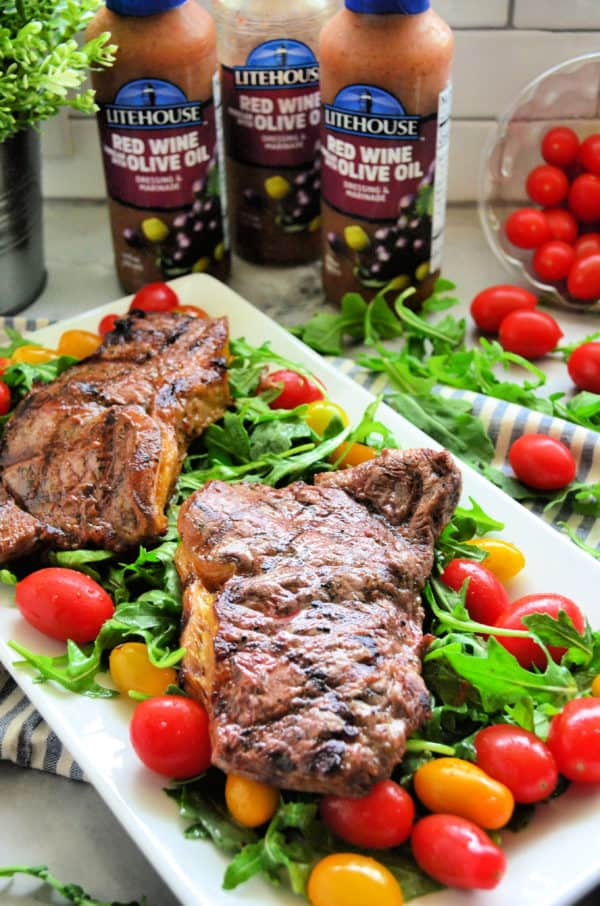 Red wine vinegar and olive oil steaks with arugula and tomato salad