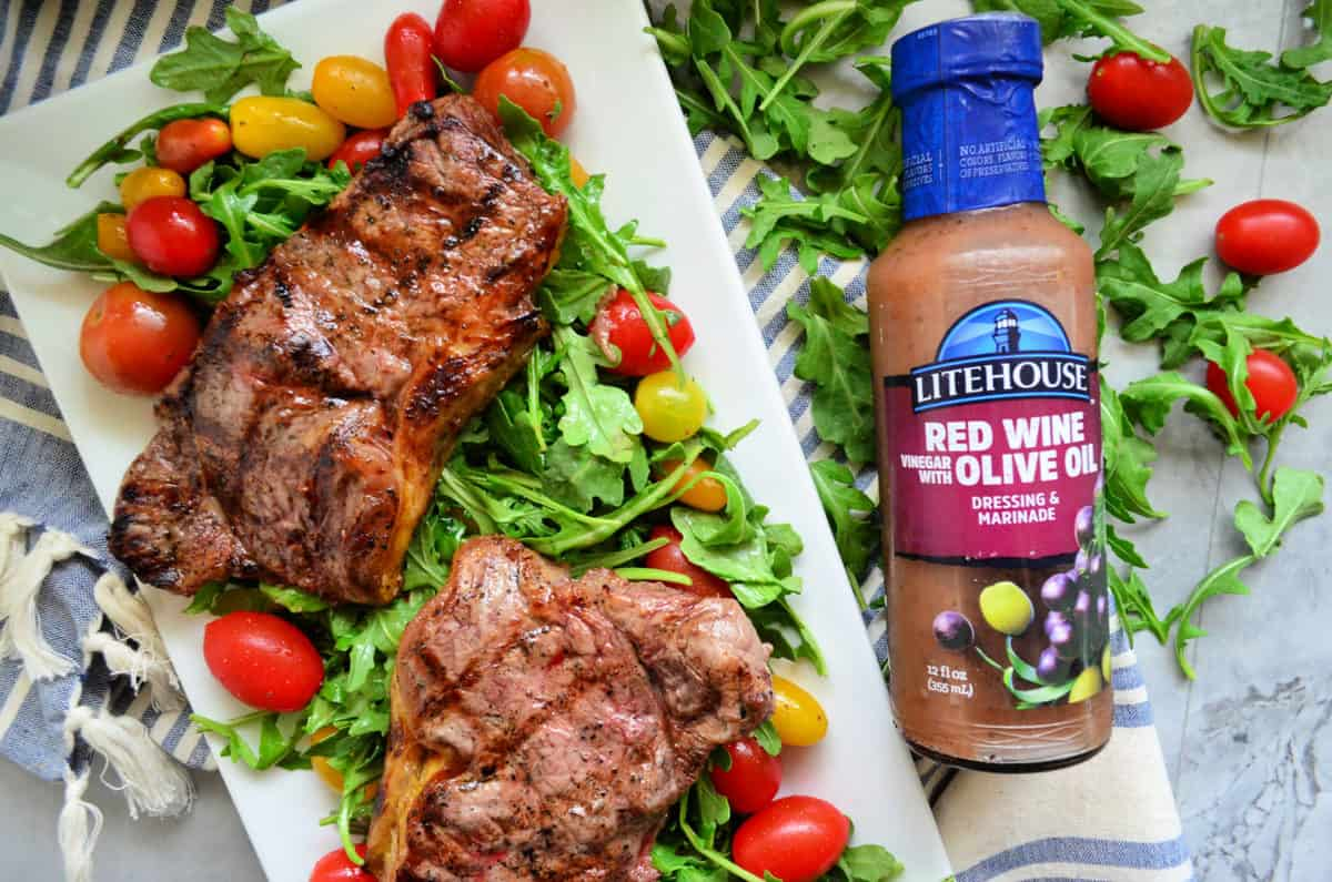2 cooked steaks over bed of arugula salad with grape tomatoes with red wine olive oil dressing bottle.