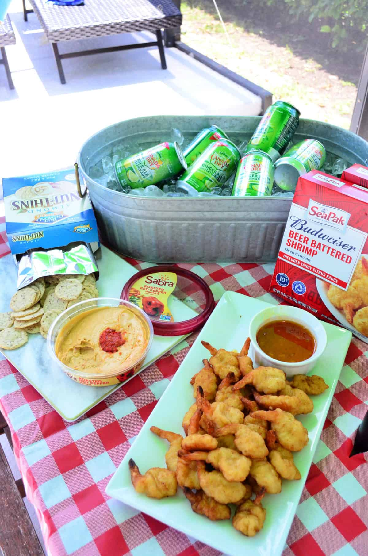 SeaPak Budweiser Beer Battered Shrimp next to iced Gingerales, hummus, crackers on picnic table.