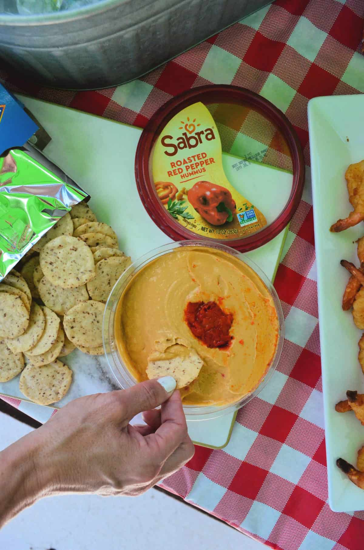 top view of hand dipping nut-thin into Sabra Roasted Red Pepper Hummus on red tablecloth.