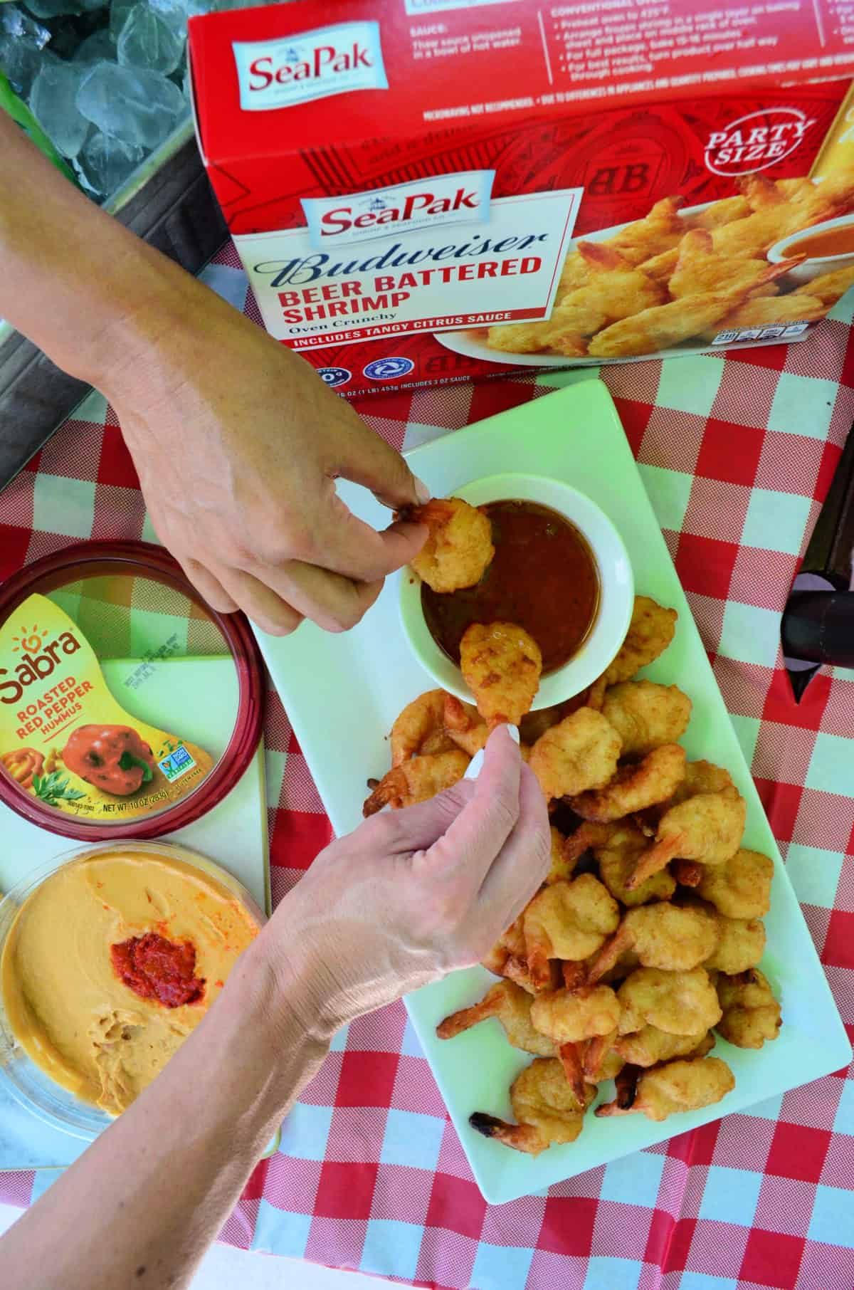 top view hands dipping SeaPak Budweiser Beer Battered shrimp from platter into sauce.