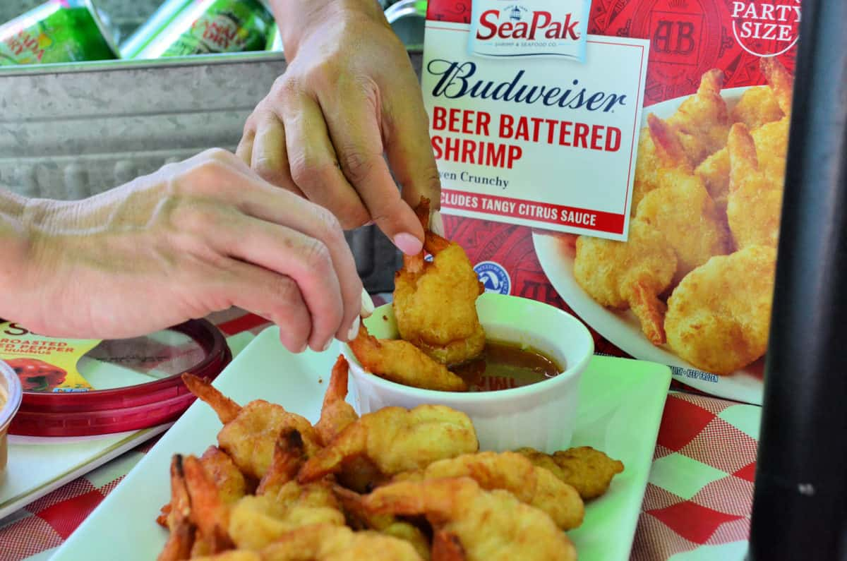 Hands Dipping SeaPak Budweiser Beer Battered shrimp from platter into sauce in front of package.