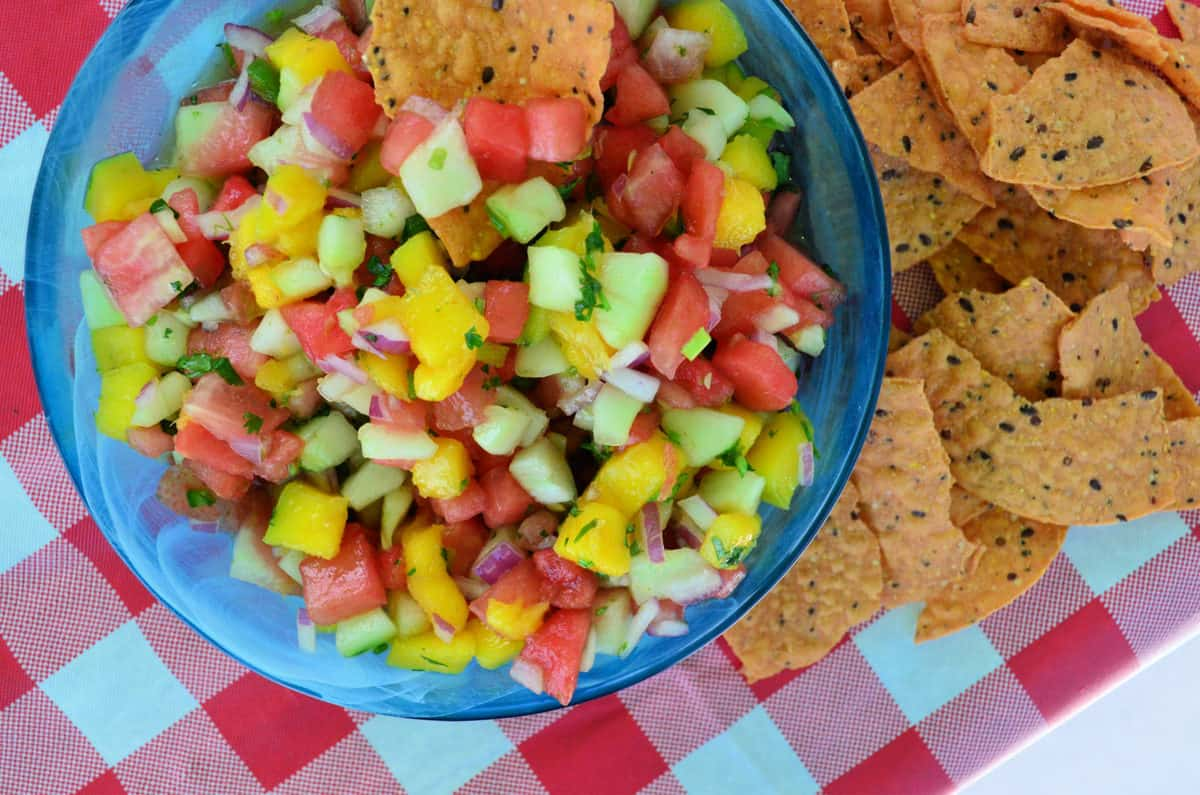 watermelon salsa with red onions, mangos, watermelon and green herbs most visible and served with chips.