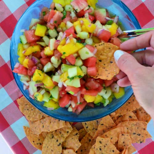 Bowl of diced watermelon, mango, onion, cilantro with hand dipping a chip into it.