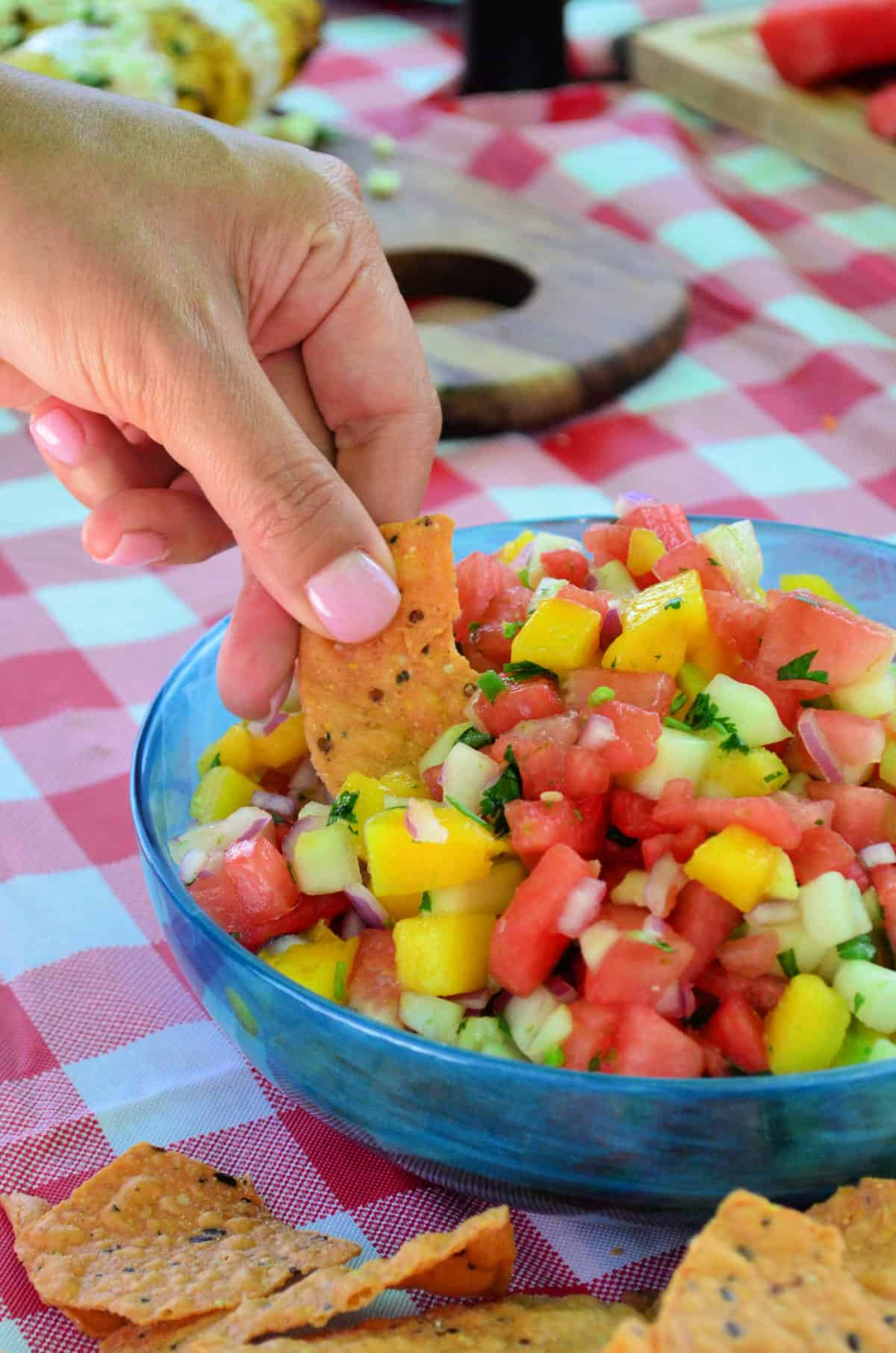 manicured hand dipping chip into watermelon salsa with red tablecloth in background.