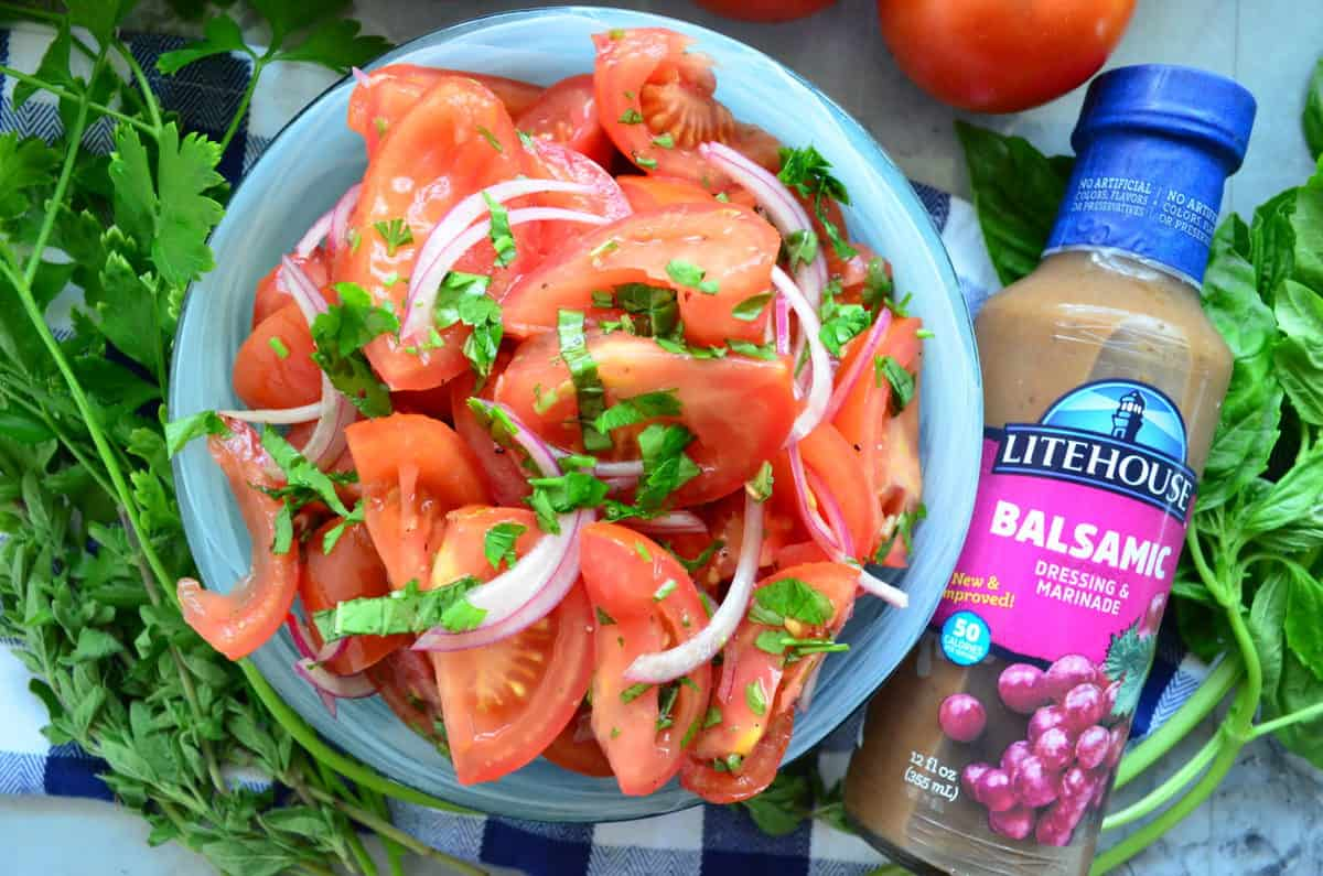 sliced tomatoes, red onion, basil, and dressing in bowl next to bottle of Litehouse Balsamic Dressing.