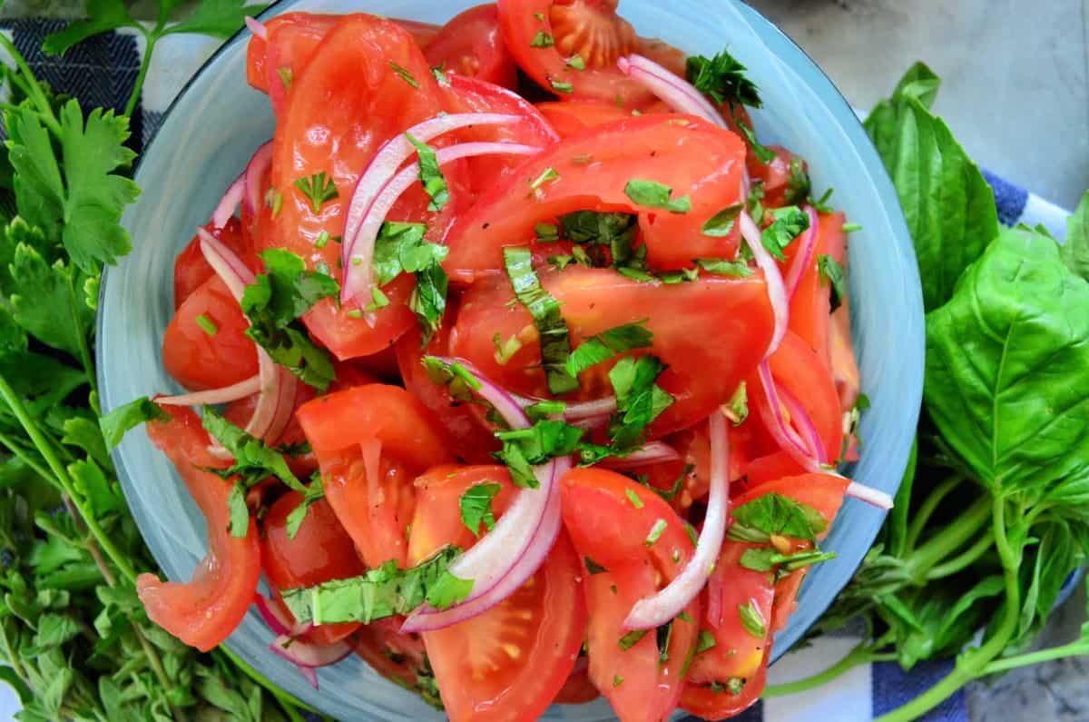 Closeup top view of tomato, onion, and basil salad next to fresh basil.
