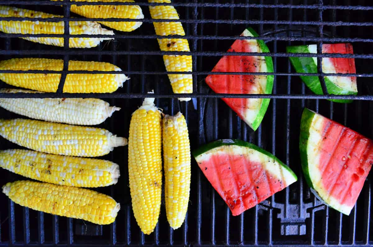 Top view of fresh watermelon slices and corn on the cob on the grill.