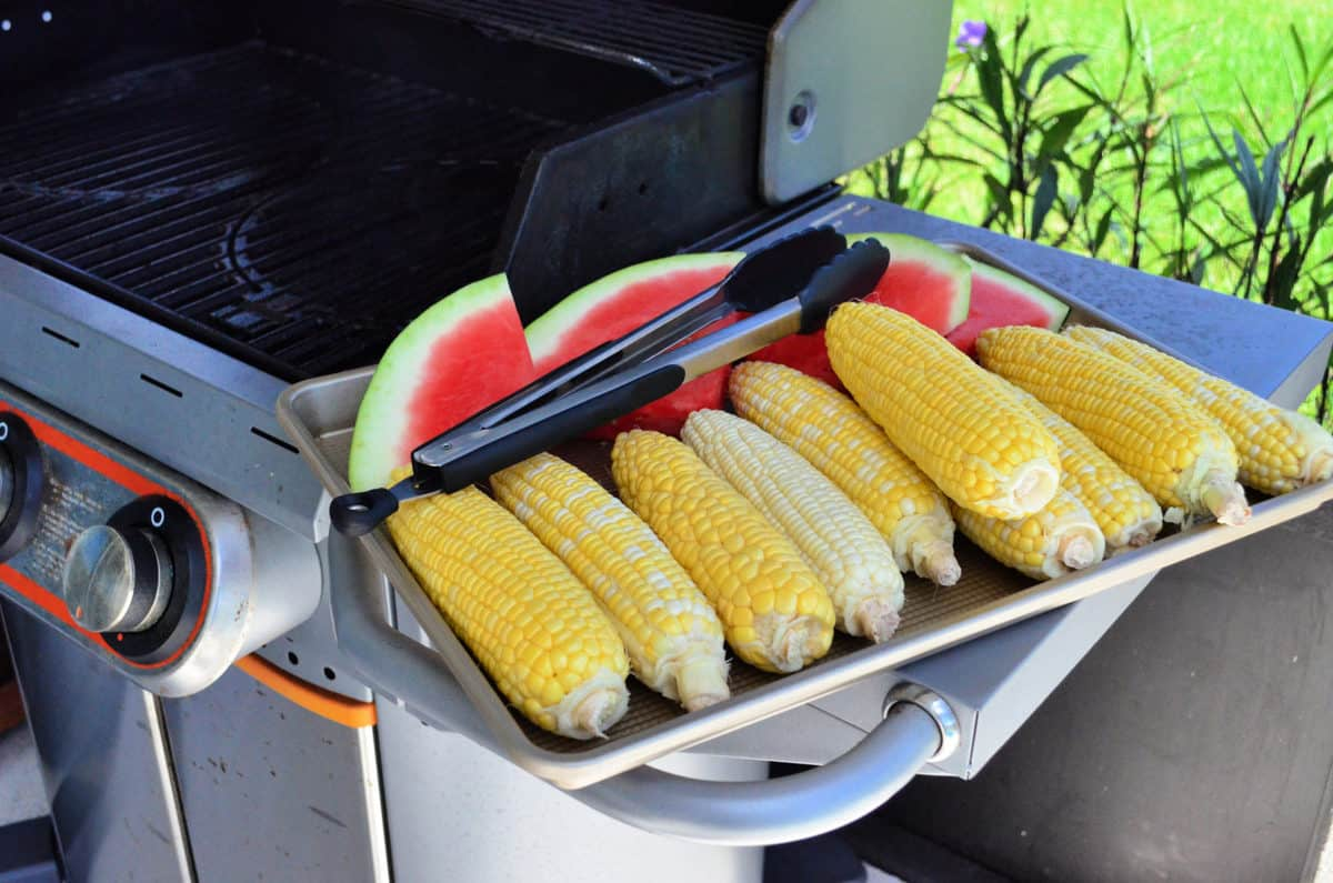 Fresh watermelon slices and corn on the cob on metal pan on grill shelf with tongs.