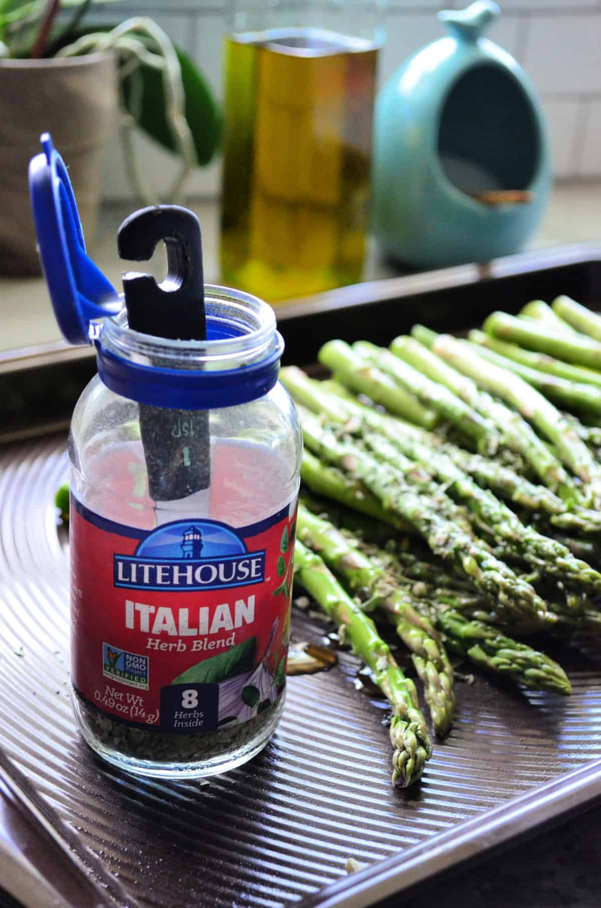 Close up of 1 tsp dipped into bottle of Litehouse Italian Herb blend set on asparagus pan.