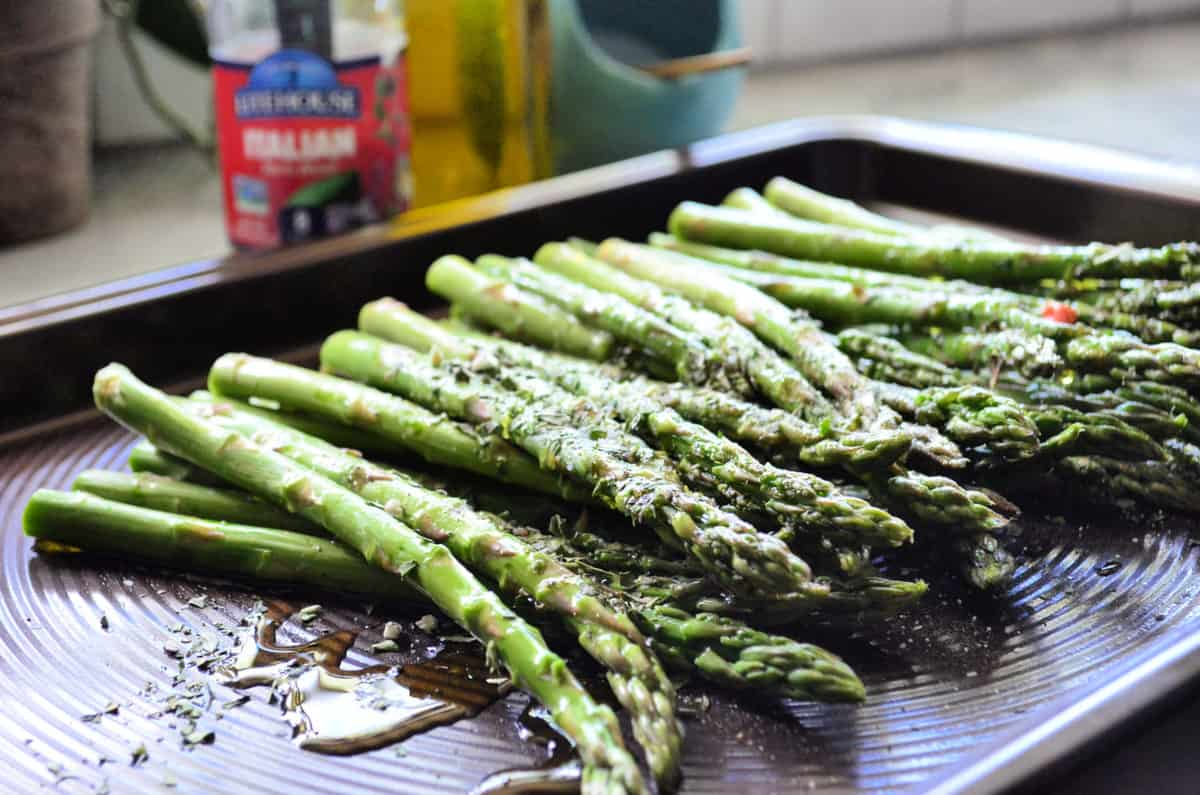 Baking pan full of asparagus glistening with oil in the light.