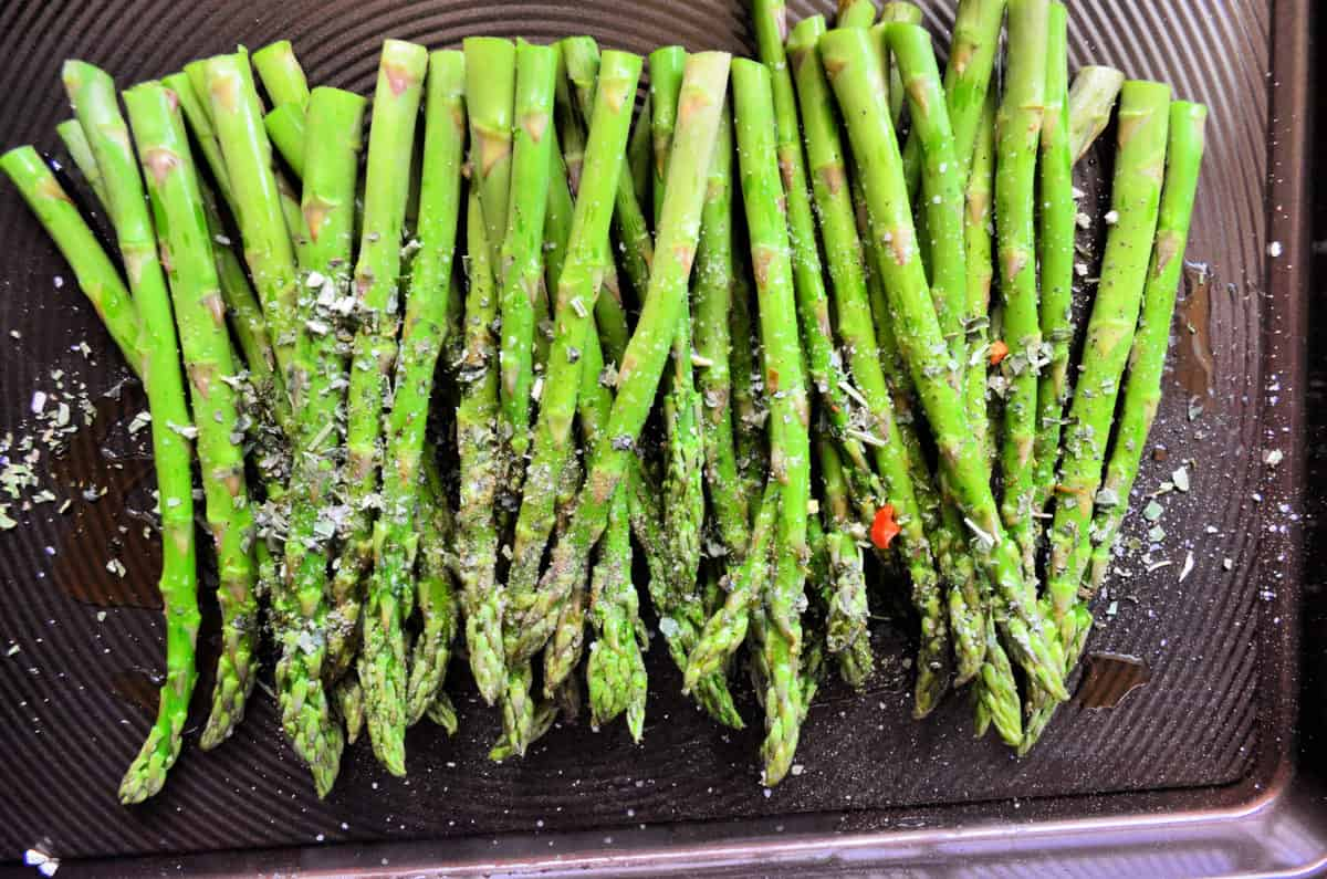 top view of grilled Italian Herb Asparagus on baking pan topped with herbs and cheese.