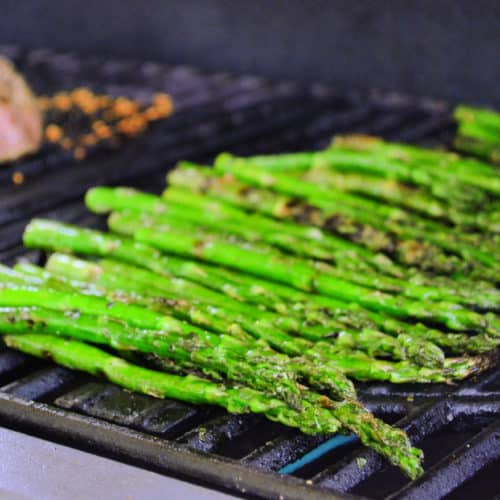 Side view of Italian Herb Asparagus on grill with meat blurred in background.
