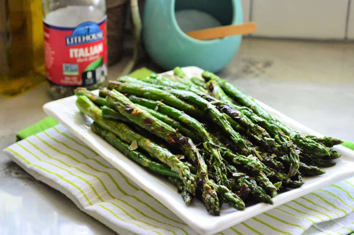 grilled asparagus on rectangular platter with bottle of italian herbs blurred in background.