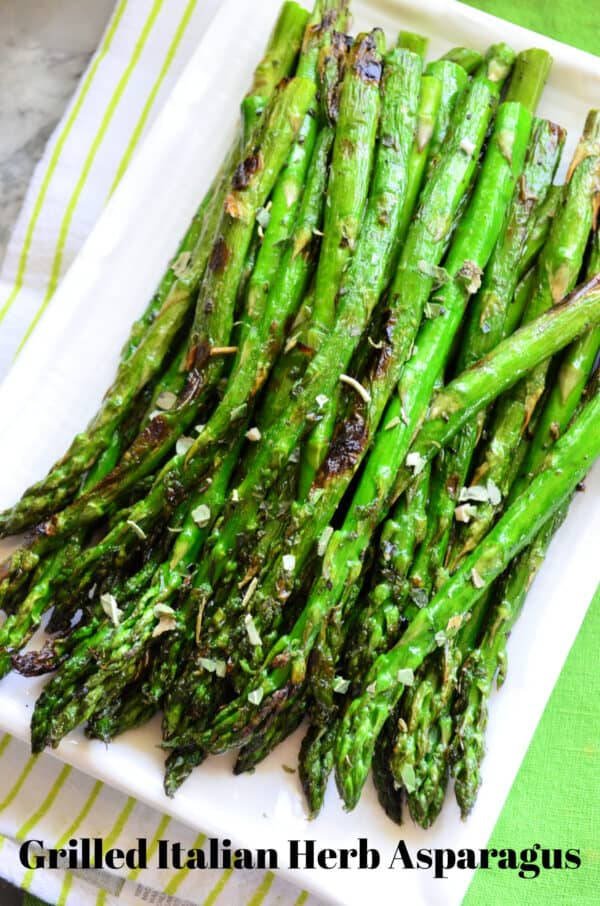 Top view of Grilled Italian Herb Asparagus on rectangle plate with pinterest title text.