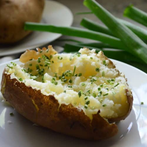 side view plated halved baked potato mashed on the inside with melted butter and chives.