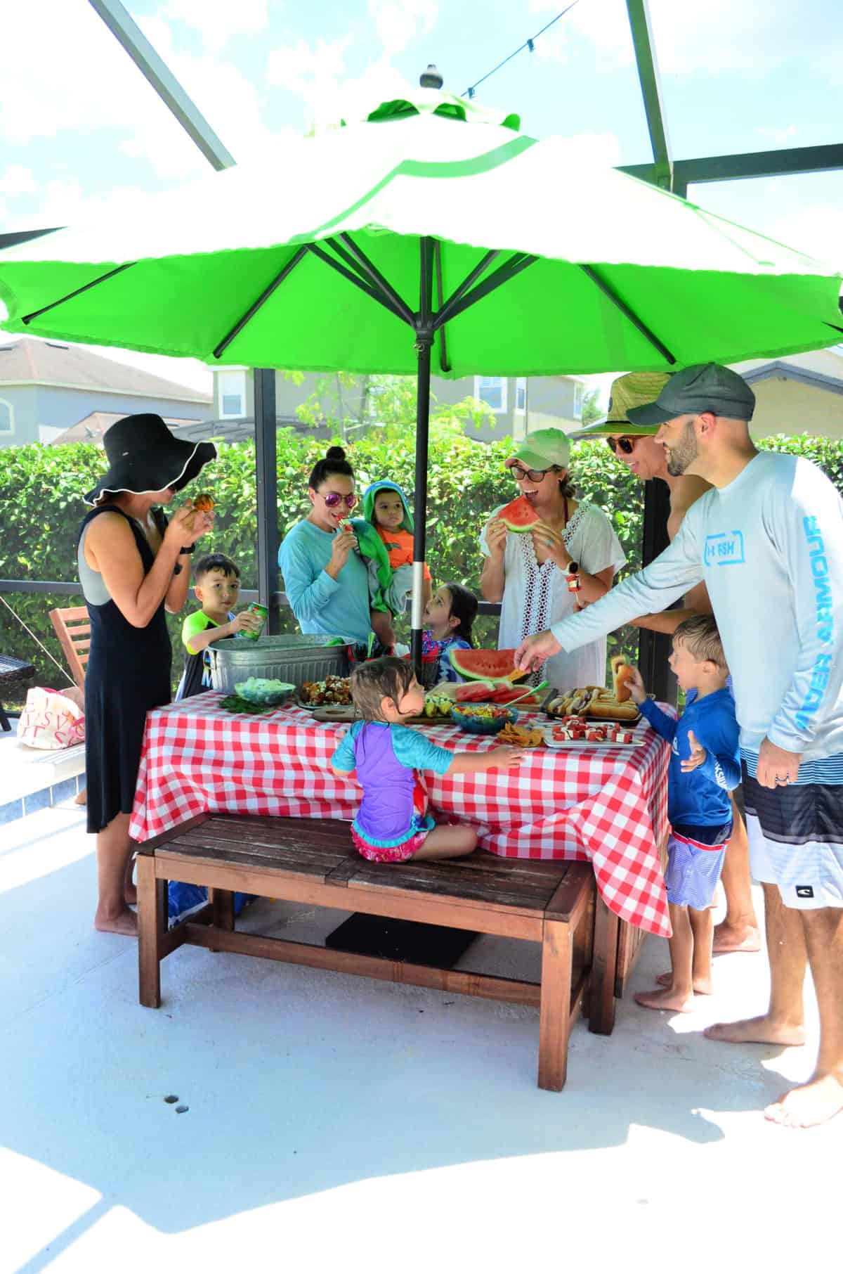 5 adults and 5 kids enjoying snacks around picnic table with red table cloth and green umbrella.
