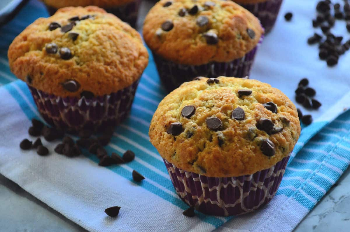 3 golden brown chocolate chip muffins on blue striped cloth scattered with chocolate chips.