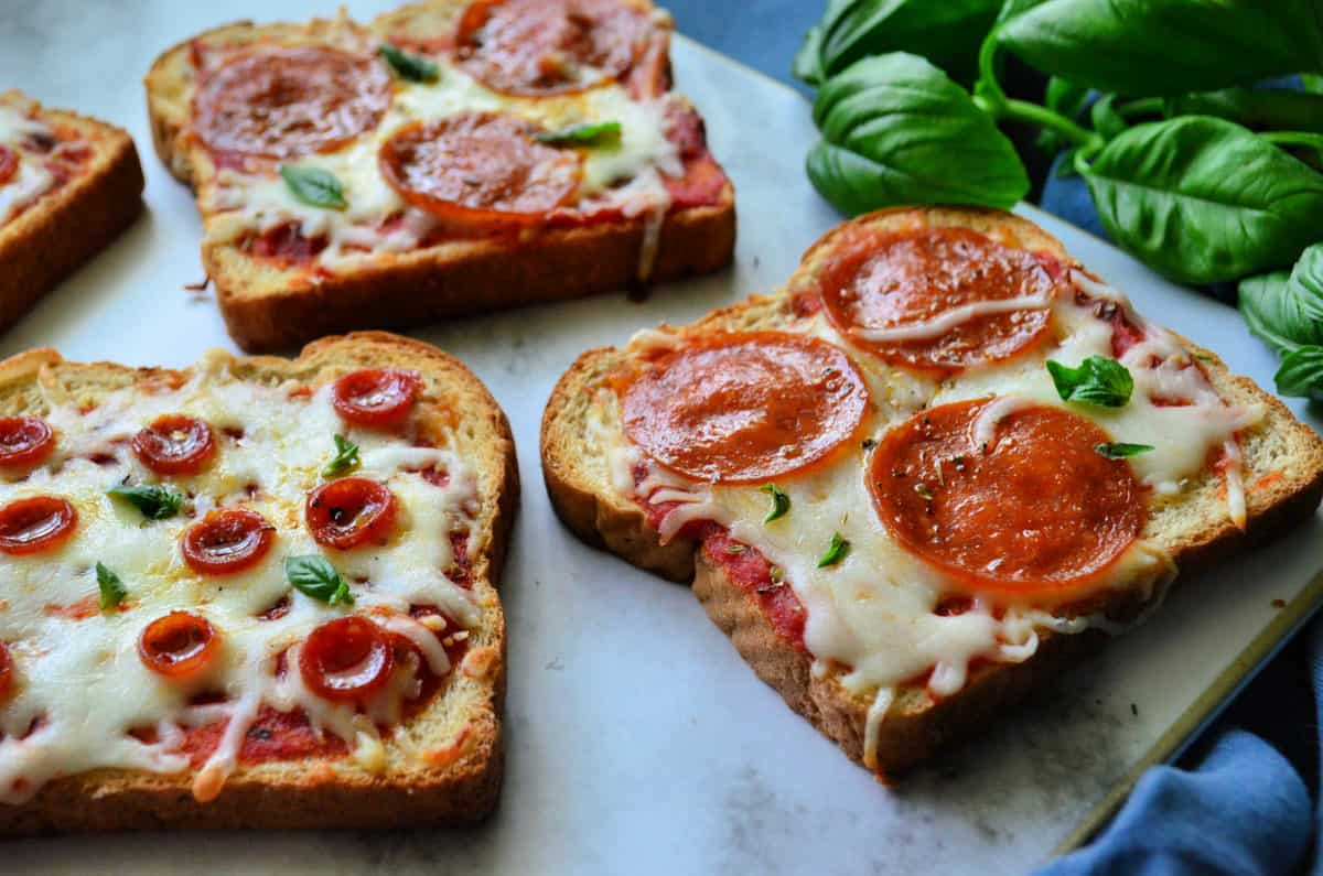 3pieces of toast with marinara, pepperoni, and cheese on countertop near basil.