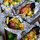 4 aluminum foil packets containing grilled mexican chicken and rice ingredients with pinterest title text.