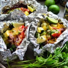 3 aluminum foil packets set next to cilantro bunch and opened to reveal veggies.