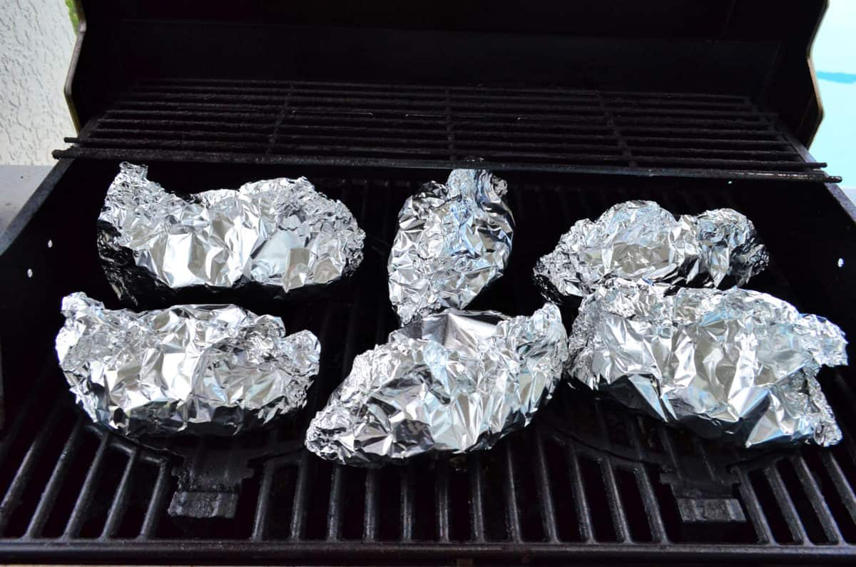 6 closed aluminum foil packets on open grill top.
