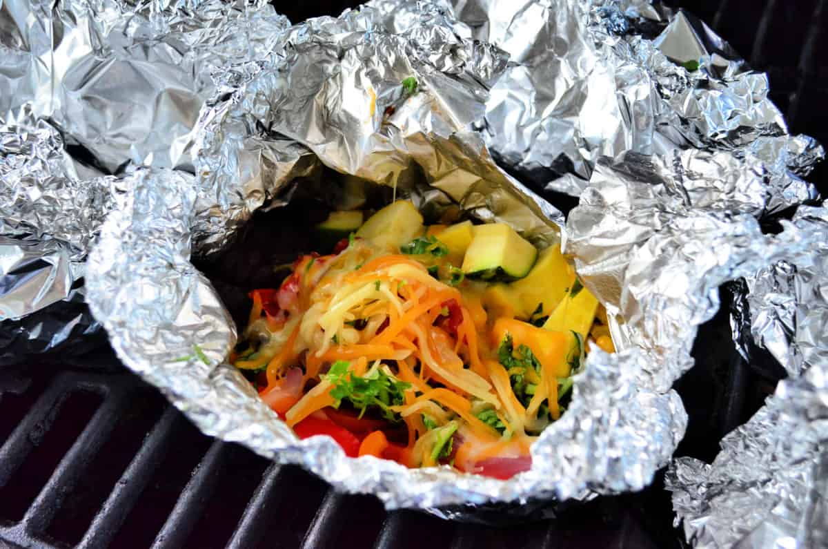 Aluminum foil packet on grill opened to show melting cheese with vegetables.