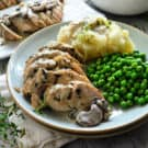 Plated turkey smothered in gravy and mushrooms with green peas and mashed potatoes.
