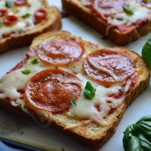 Close up of toast pepperoni pizza next to basil.