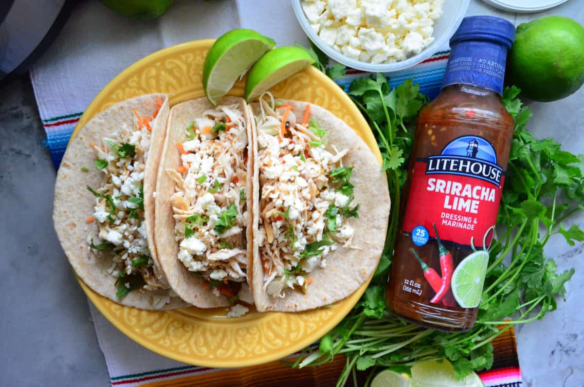 Top view of 3 plated shredded chicken tacos next to bottle of Litehouse Sriracha Lime Dressing.