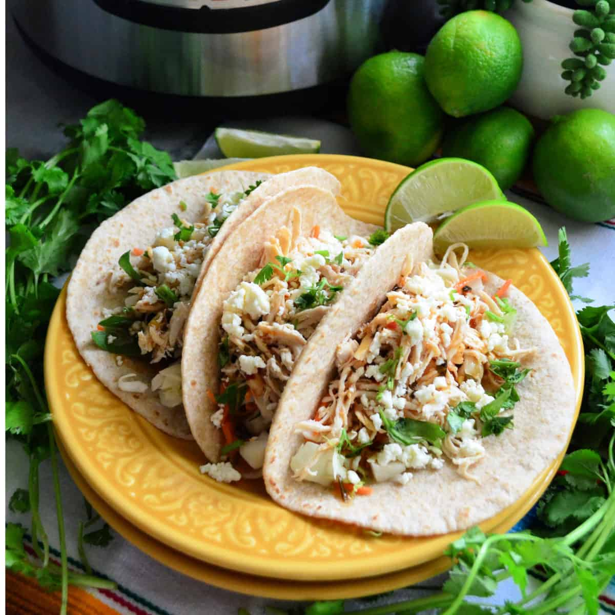 3 flour tortilla tacos filled with shredded chicken, cheese, and herbs surrounded by limes and cilantro.