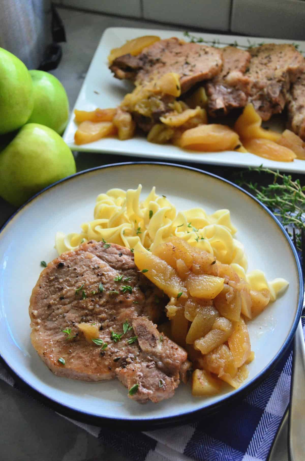 Plated sliced pork chops with cooked apples, egg noodles, and platter of pork chops in background.
