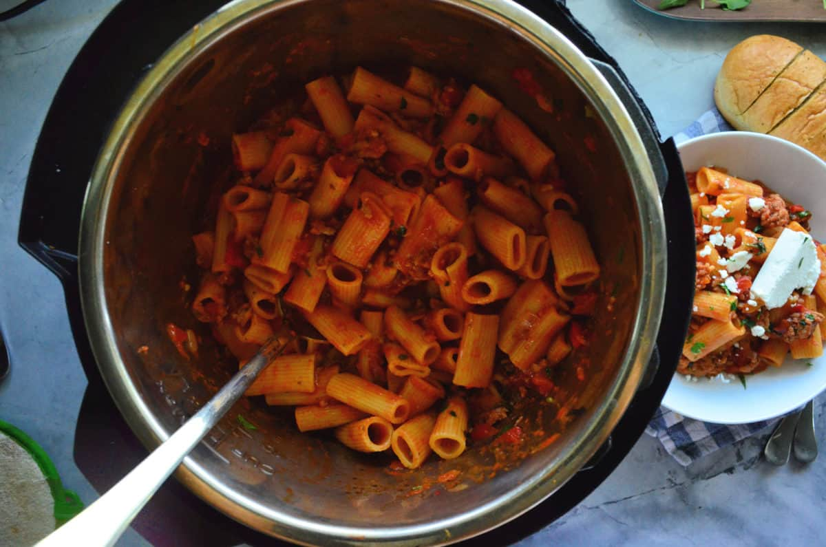 top view of rigatoni noodles in instant pot with red meat sauce.