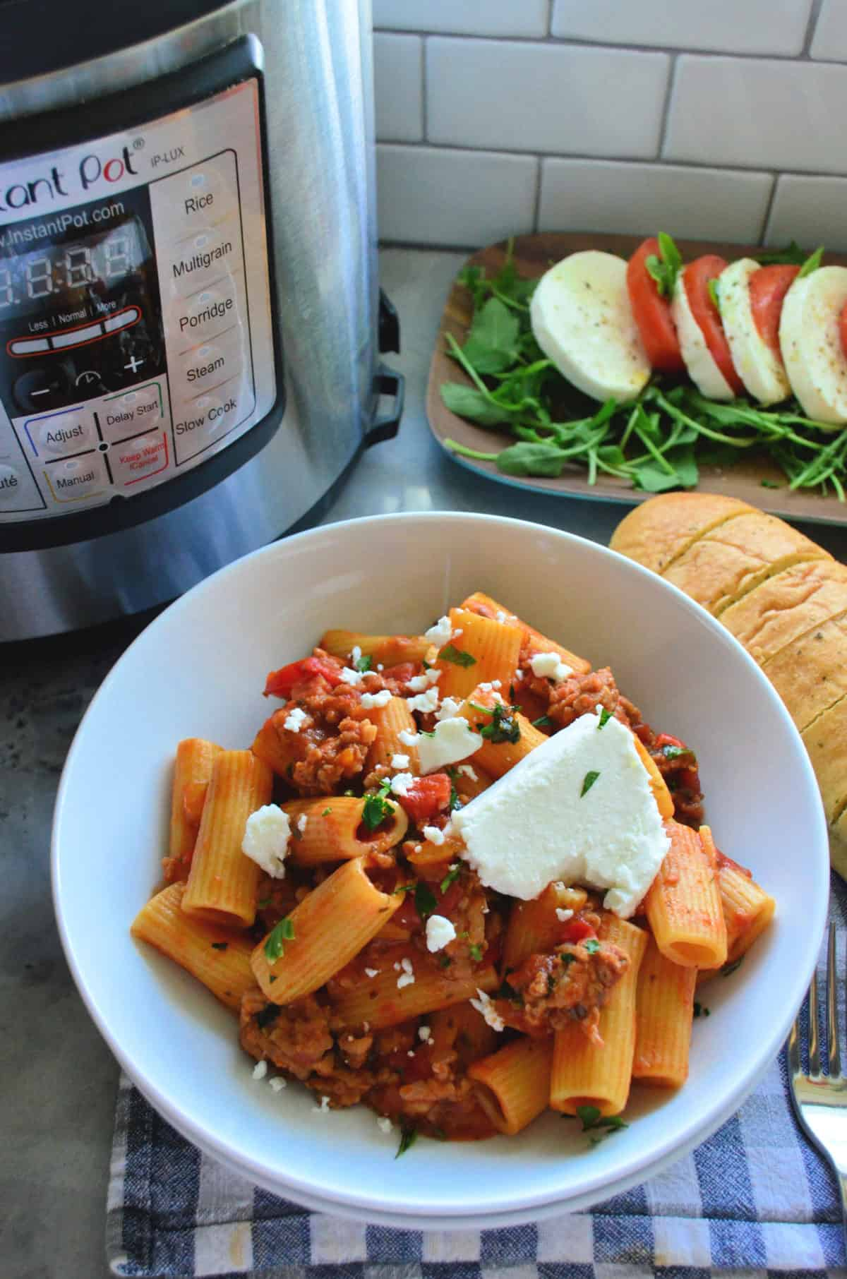 Plated Rigatoni noodles with meaty red sauce, basil, and cheese in front of instant pot and caprese platter.