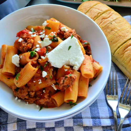Bowl Rigatoni in meaty red sauce with goat cheese on placemat with forks and french bread.