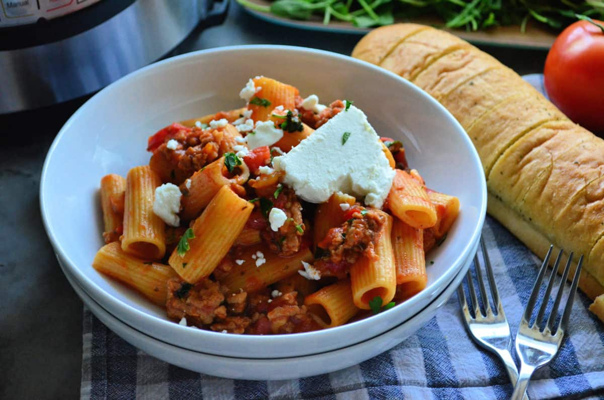 Plated Rigatoni noodles with meaty red sauce, basil, and cheese in front of baguette and tomato.