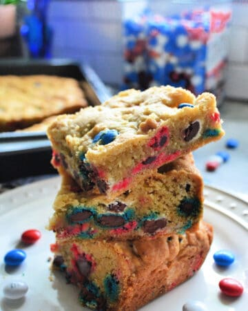 Stacked M&M Cookie Bars with red, white, and blue M&M's in the background.