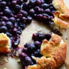 Close up of cooked blueberries in golden brown pastry crust with pinterest title text.