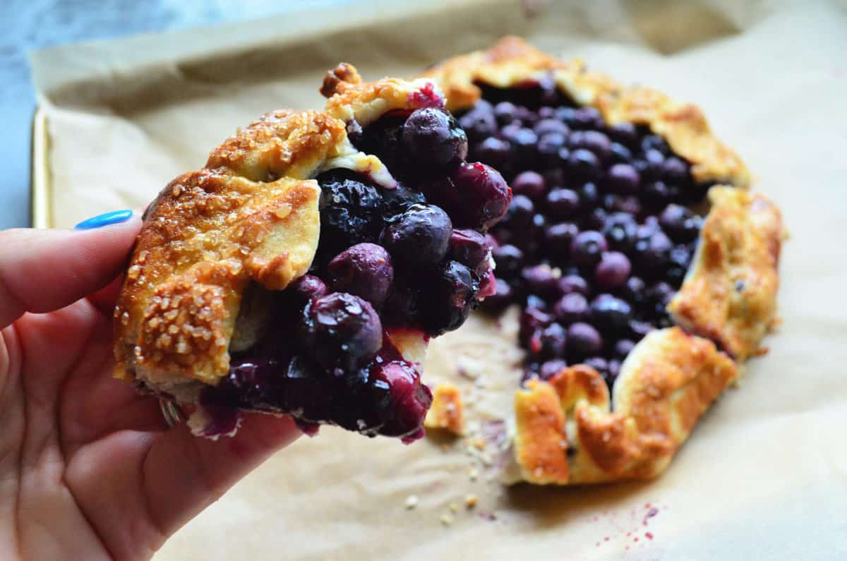 close up piece of blueberry crostata with bite missing and remaining crostata blurred in background.