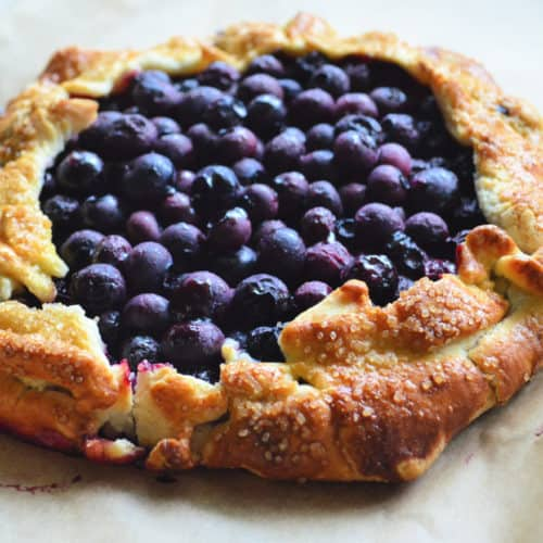 Top View of cooked blueberries in circular golden brown pastry crust.