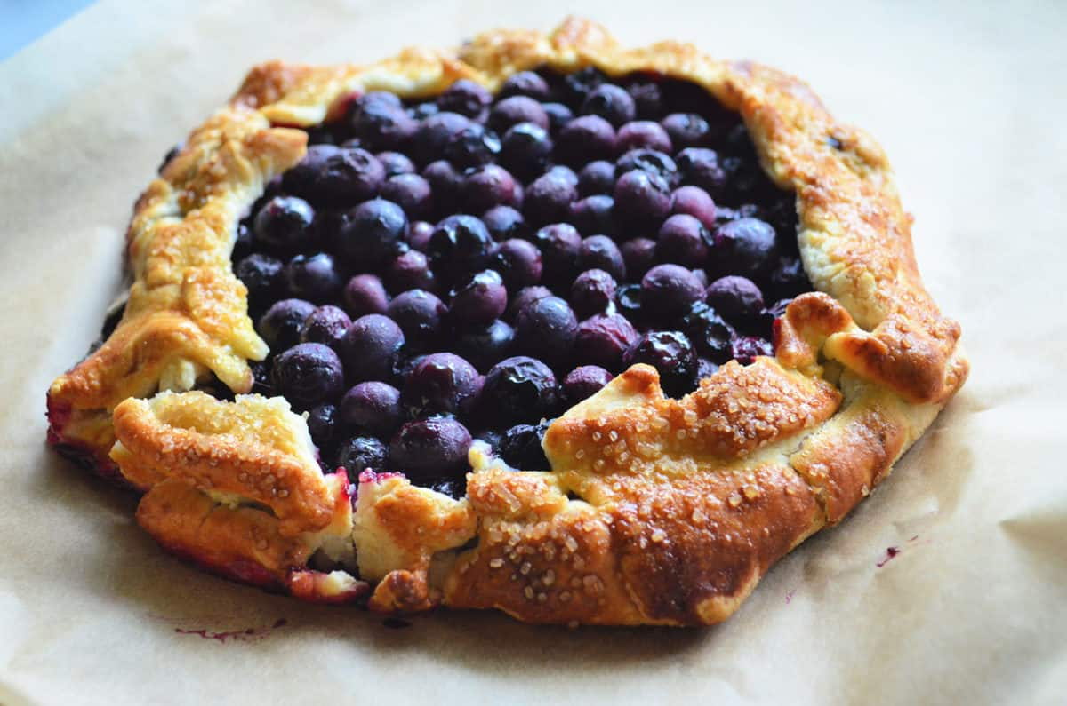 top view of flakey uneven pie crust with cooked blueberries as filling.