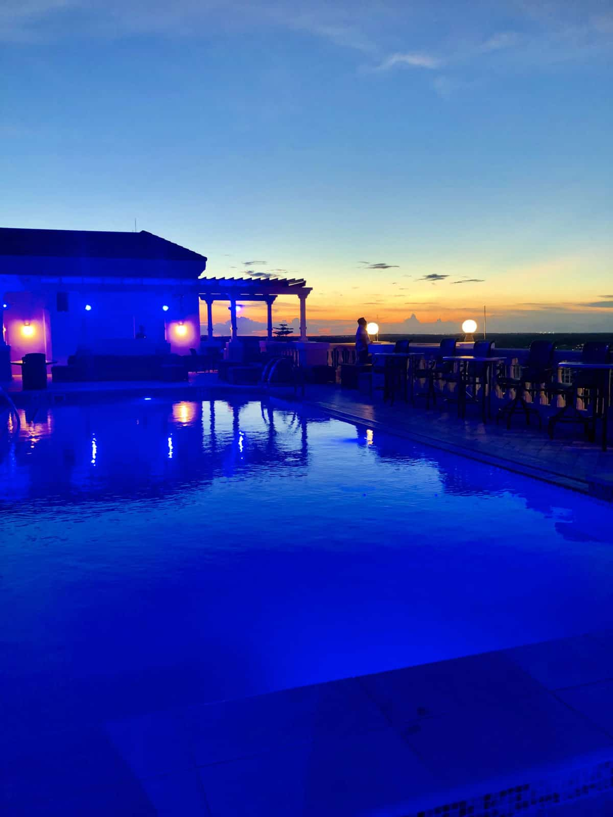 Blue filtered pool and pool house with patio seating during sunset.
