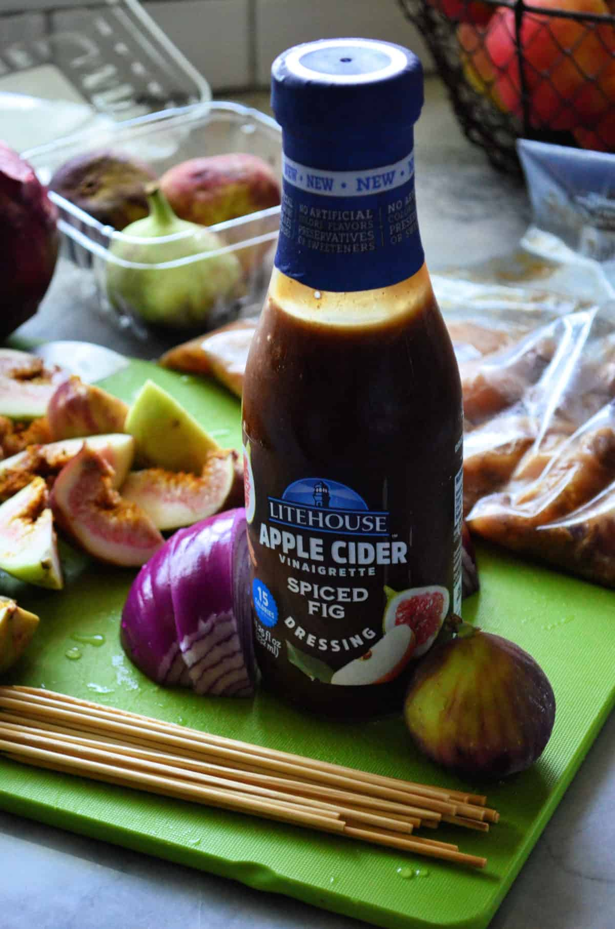 Bottle of Litehouse Apple cider vinaigrette spiced fig dressing on cutting board with skewer ingredients.