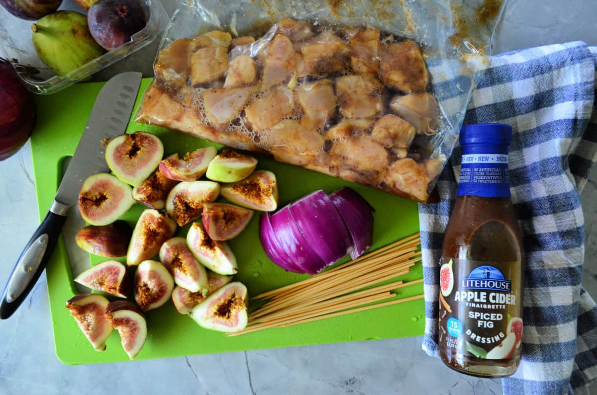 bag with marinading chicken, quartered fresh figs, sliced red onion, dressing, and pasta on cutting board.
