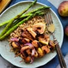 Grilled Chicken, red onion, and figs skewered over bed of rice served with asparagus on plate.