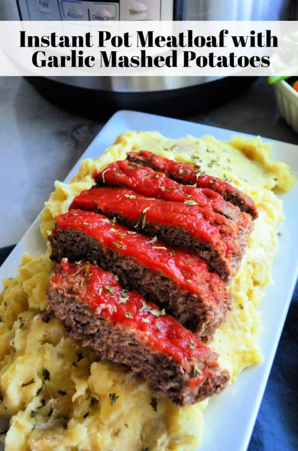 Platter of Golden herbed mashed potatoes topped with meatloaf dripping with red sauce. Pinterest title text.