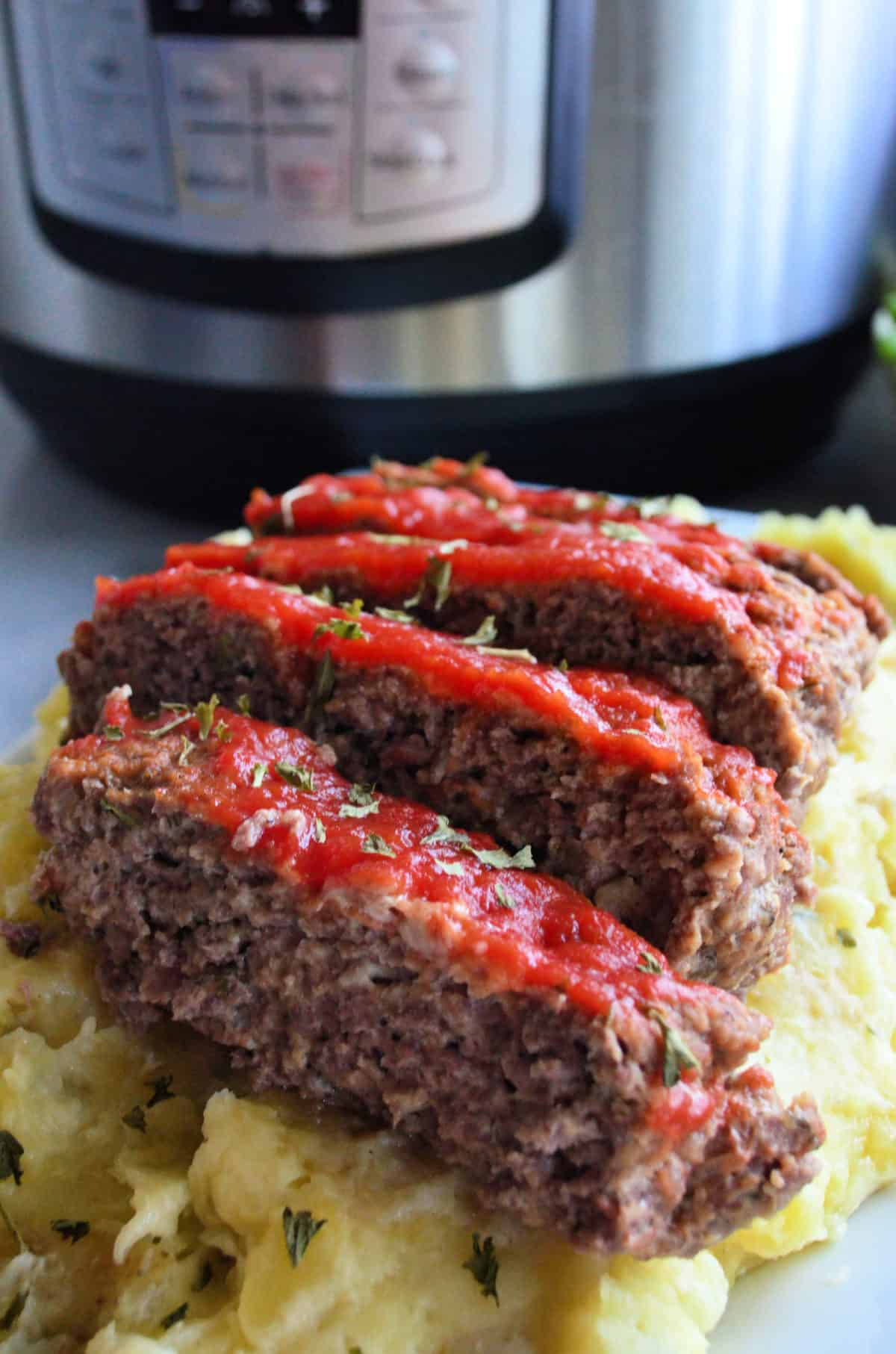 closeup front view of sliced meatloaf topped with herbs and red sauce over mashed potatoes.