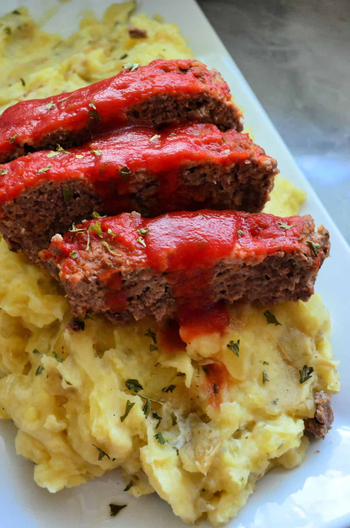 closeup of sliced meatloaf topped with herbs and red sauce over mashed potatoes.